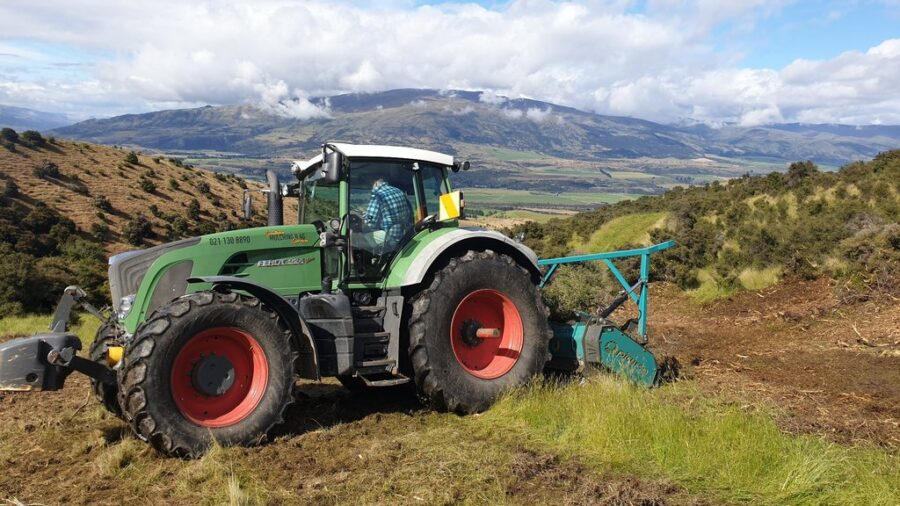 Fixed tooth forestry mulcher with hydraulic pusher bar.
