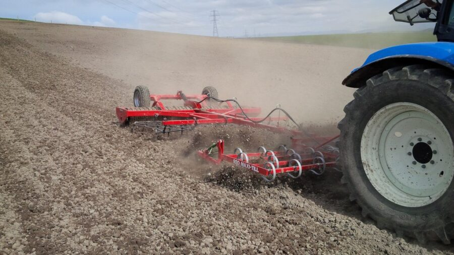 Spring tine cultivator towing Cambridge roller