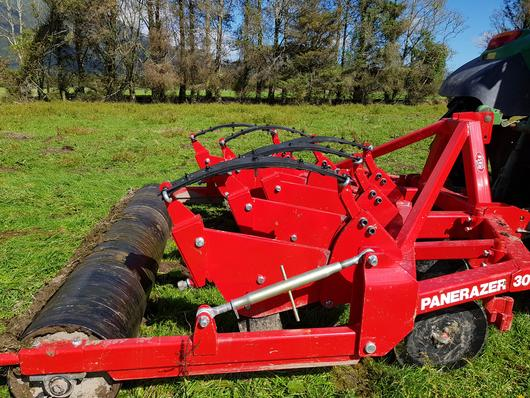 Auto-reset aerator with coulters and rear roller